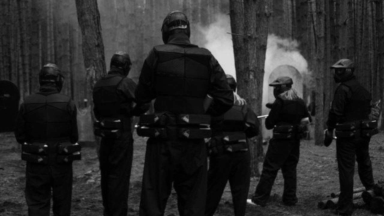 Players Gather Toether In Woods Wearing Black Paintball Kit