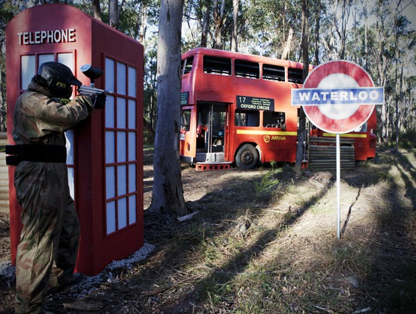 Paintball Player Behind Telephone Box Fires at Enemy in Bus