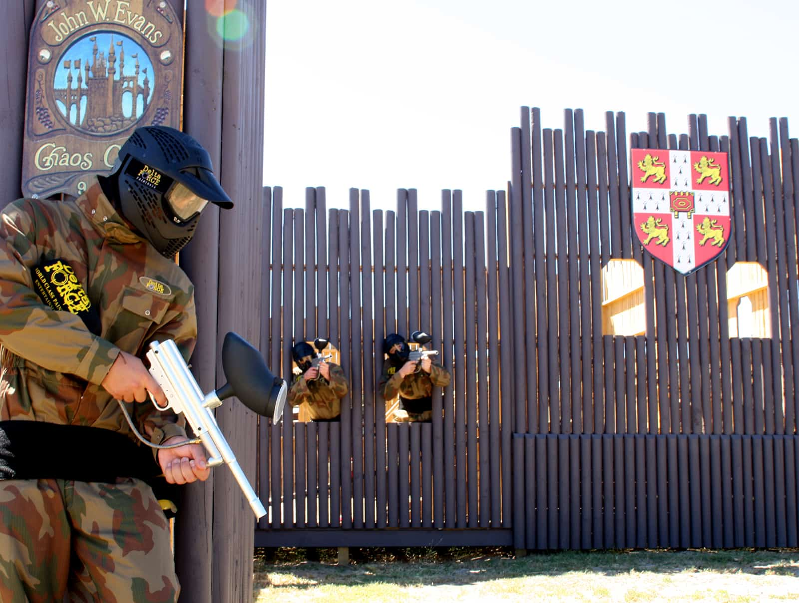 Paintball Player Hides Behind Ramparts From Two Castle Defenders