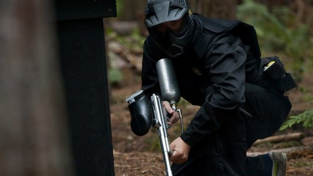 Delta Force Player Crouches In The Woods Behind Cover