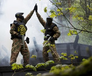 Two players high five, one wearing yellow target vest