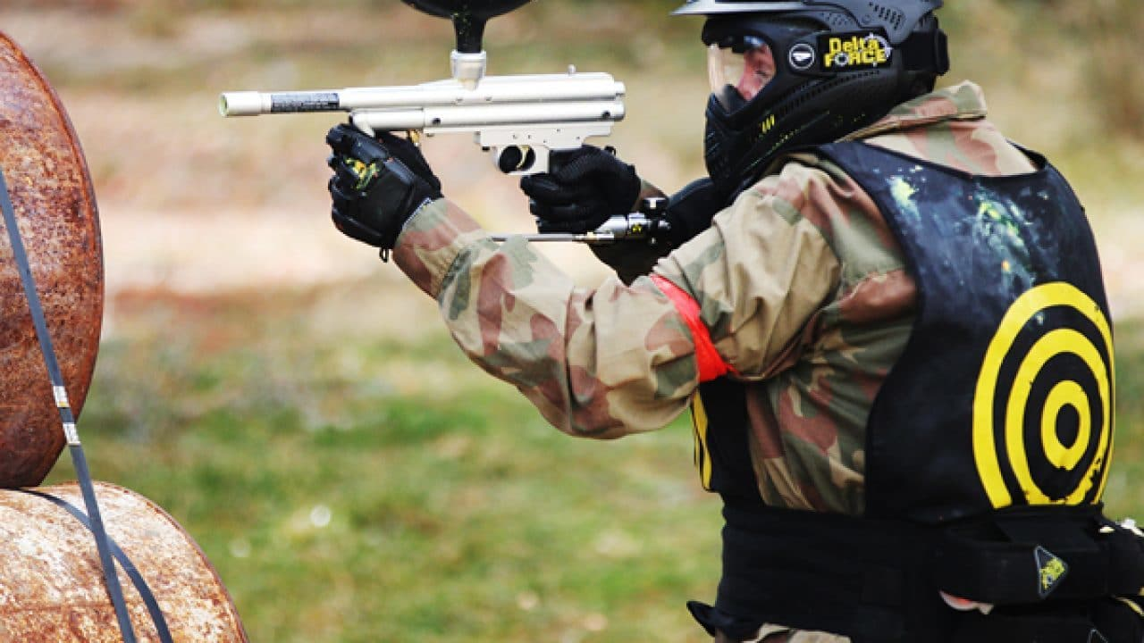 Delta Force player takes aim behind Speedball barrel