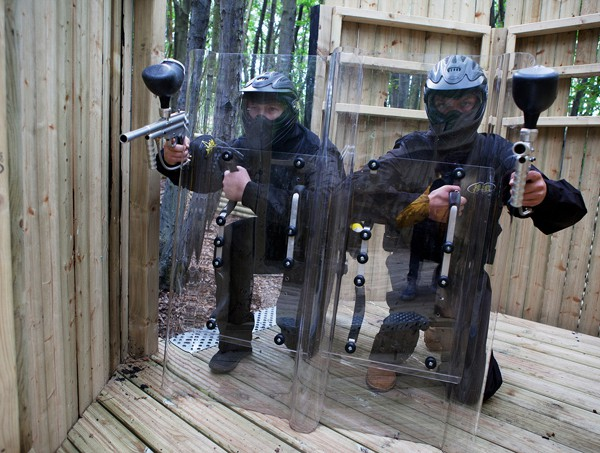 Two players crouch ready behind paintball shields