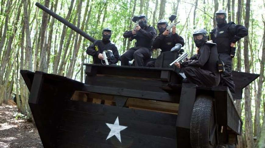 Delta Force players pose upon tank