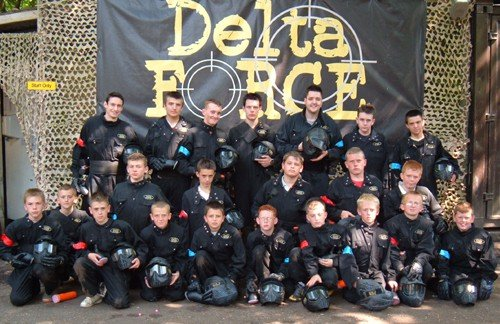 Boys Posing In Front Of Delta Force Paintball Banner