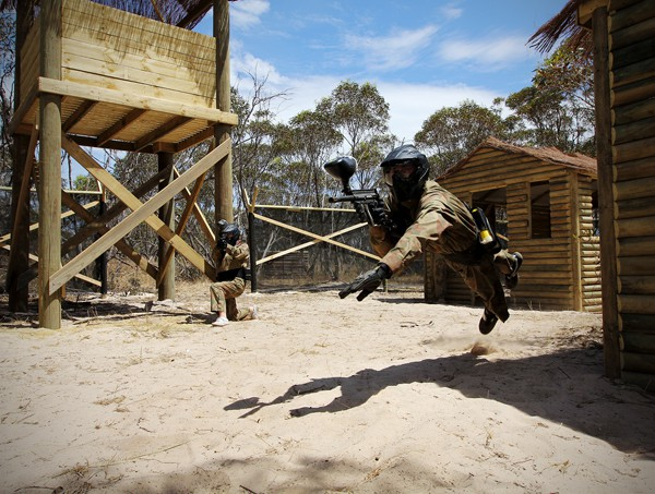 Player Leaps Mid-Air Holding Paintball Gun Vietcong Village