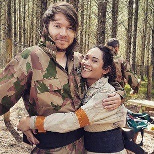 Couple embrace in paintball gear