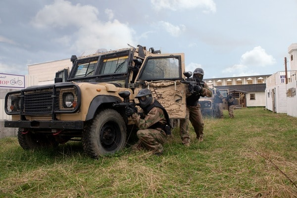 Paintball players take cover around armoured Jeep