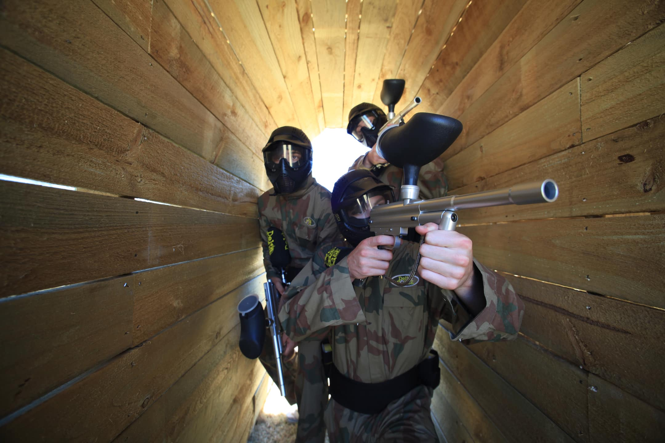 Delta Force Paintball Players Pose In Narrow Walkway