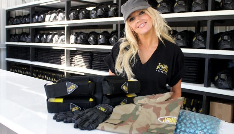 Smiling Cashier Poses with Paintball Equipment