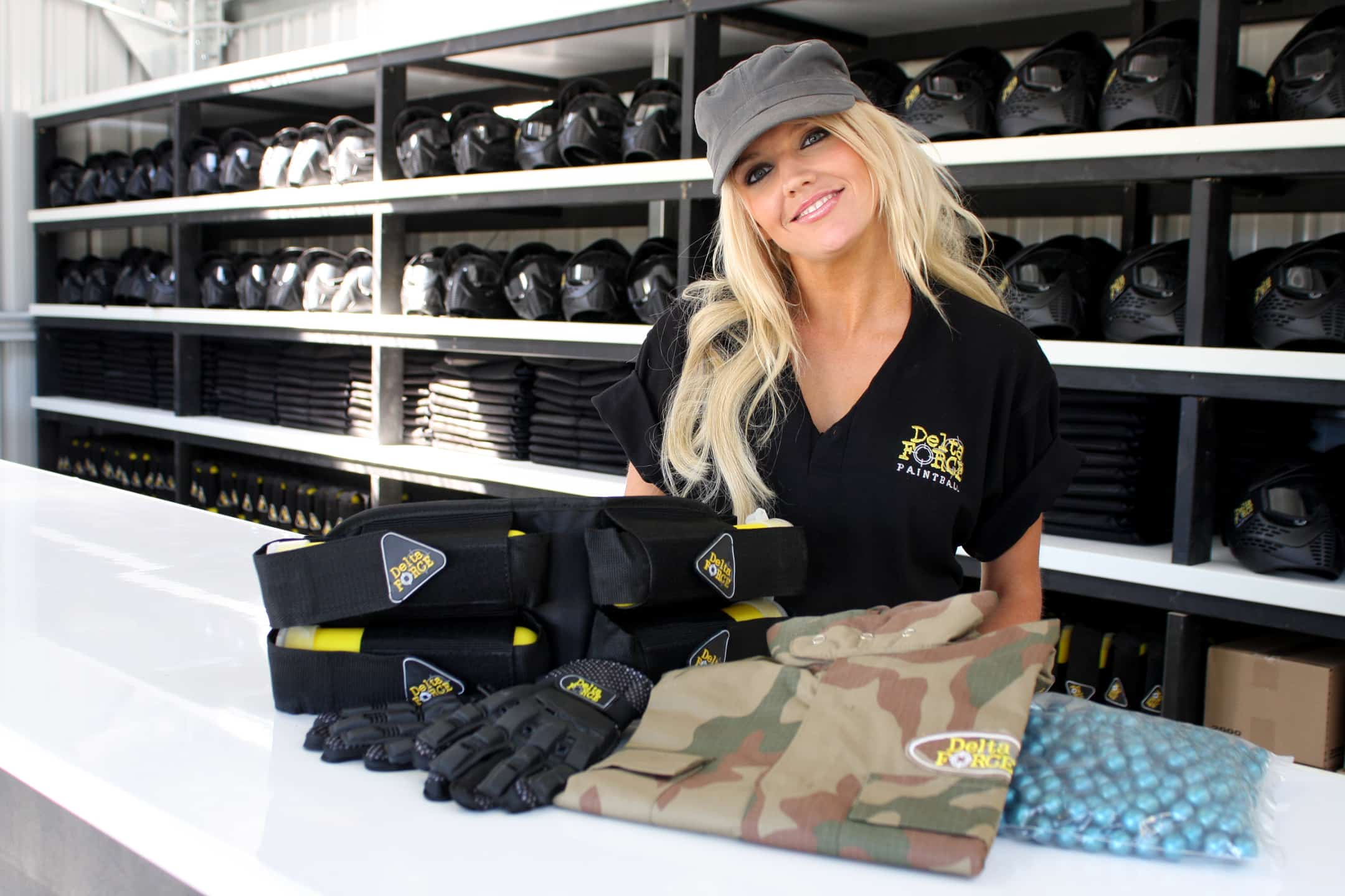 Smiling blonde cashier poses with paintball equipment