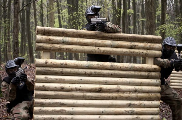 Paintball Players Use Fence As Cover