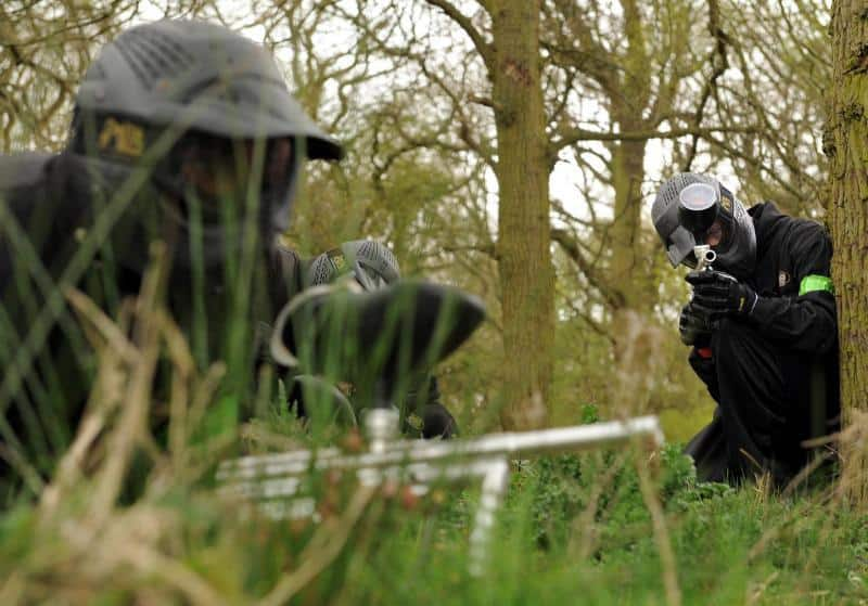 Two Paintball Players Hiding in the Grass