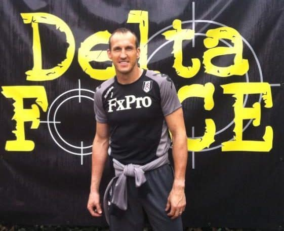Fulham player poses before Delta Force logo