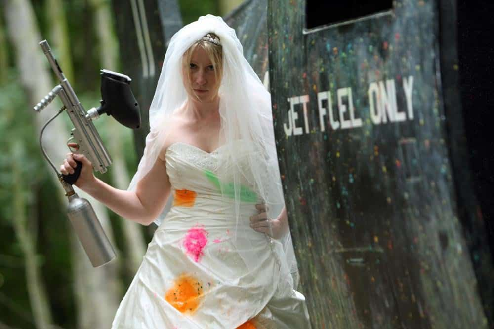 Paint-splattered bride poses with gun