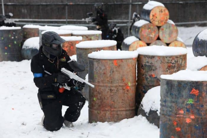 Paintball player takes cover behind snow-covered barrels