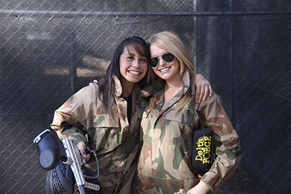 Two women smile with Delta Force guns