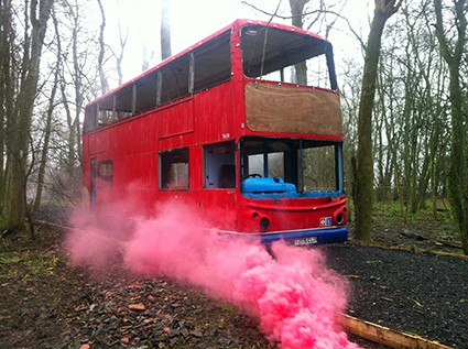 Red London double-decker bus engulfed in smoke