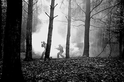 Players in the distance advance through smoke-ridden forest