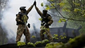 Two Paintball Players High Five with Each Other