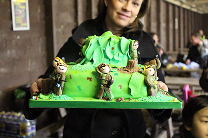 Woman holds up green paintball birthday cake