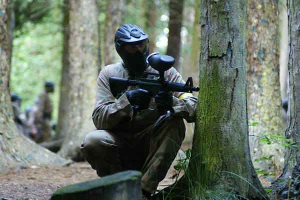 Player crouches behind tree with M16