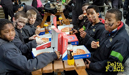Kids eating pizza at Delta Force base camp