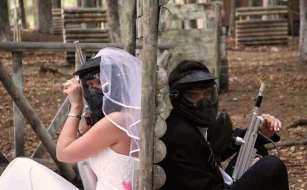 Couple pose for paintball wedding