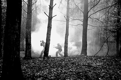 Players weave through trees and smoke in black and white
