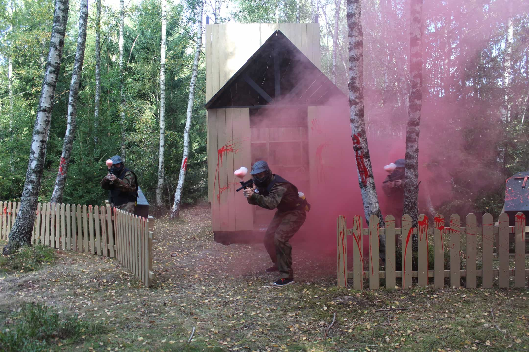 Three paintball players advance past blood-splattered fence