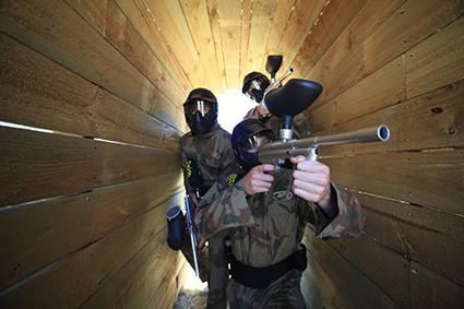 Three Players Advance Through Wooden Tunnel in Paintball Edinburgh