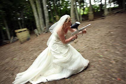 Bride crouches on the move with gun