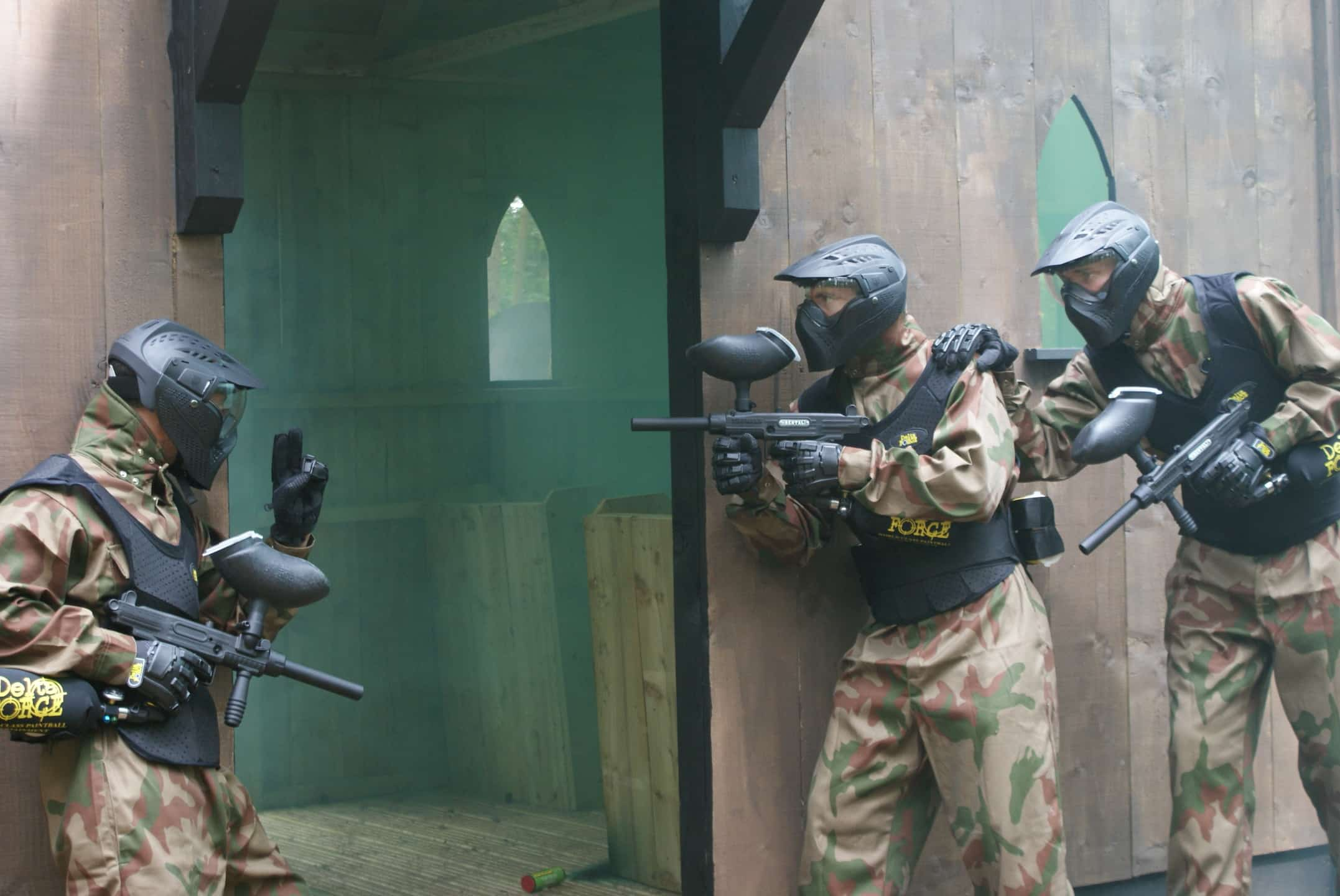 Three paintball players prepare to rush entrance to Crypt