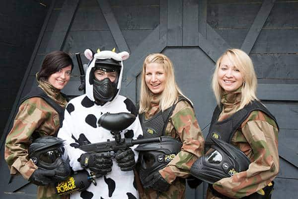 Hen Dressed In Cow Onesie With Friends In Paintball Kit